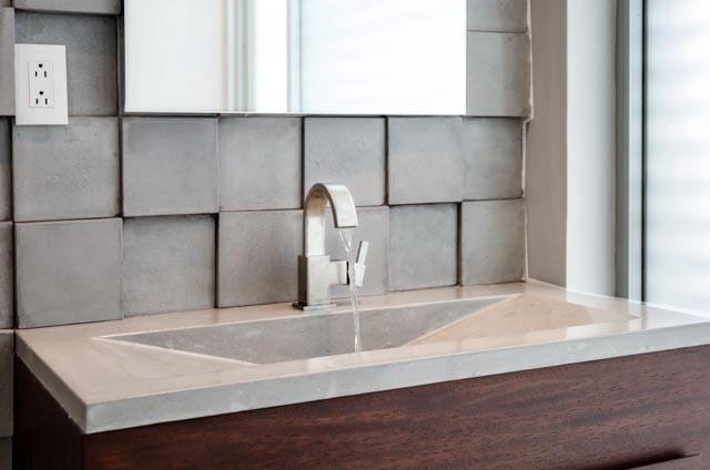 Moderno lavamanos en tonos neutrales y aplique de pared. Todo hecho con concreto.