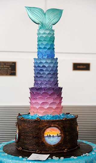 """The Mermaid and the Sea - I made this cake for a cake competition in Denver, CO.  The theme was """"Under the Sea"""" and I decided to do a giant mermaid tail and fin coming out of the water made with blue piping gel and white buttercream.  I love cakes with windows so I did 4 different scenes in the portholes."""