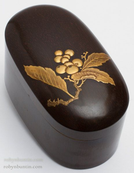 Fine Taisho Period (1912-1926) Japanese lacquer ink box (suzuribako). This oval suzuribako is very unusual in shape and in surface treatment. The surface is painted wood grain with a gold high relief painting of a branch of kumquats. There is a single tray inside. The artist's name (Hisayoshi) is signed under the cover in gold.