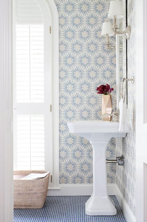 Breathtaking powder room boasts walls clad in white and blue wallpaper, Zoffany Spark Wallpaper, lined with a frameless mirror illuminated by polished nickel sconces fitted with white pleated shades over a white pedestal sink and a CB2 Puckr Vase atop a blue penny tiled floor finished with white grout.