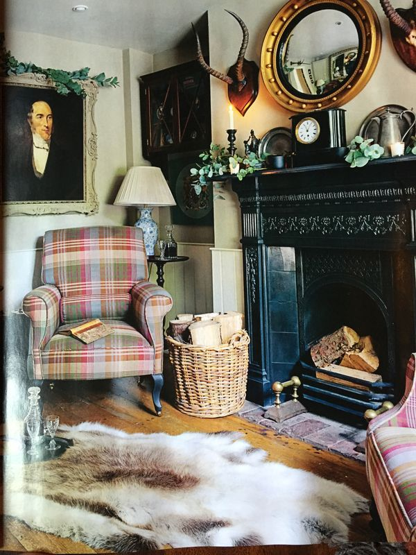 Charming sitting area with a masculine look.  I like the black mantel and the Regency period gold leaf circular convex mirror.