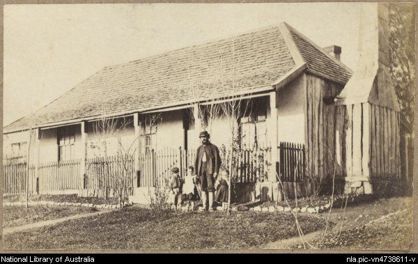 Man with three children in front garden of rendered slab house with shingle roof and picketed veranda, Hill End, New South Wales, ca.1872 [...
