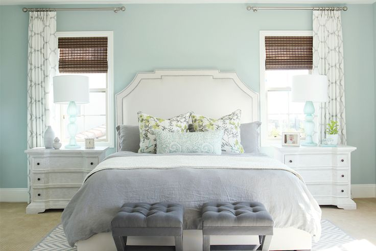 Pretty bedroom with blue walls framing an ivory headboard with nickel nailhead trim on queen bed dressed with white and gray bed linens topped with blue and yellow floral pillows and a seafoam blue lumbar pillow with gray velvet tufted x-stools at the foot of the bed.