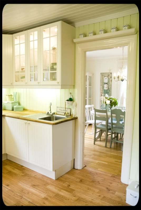 Pretty Norwegian kitchen. I'd remove the tiny fussy boxes above the doorway and sconce near the sink, add some glorious art and plants...