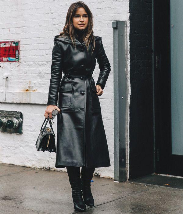 Miroslava Duma com look todo preto e trench coat de couro.