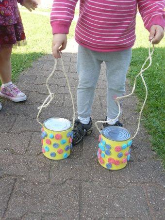 Avec mes 3 petits acrobates, nous avons fabriqué des échasses...  Le matériel :- 2 boites de conserves- une grande feuille de cartoline de couleur- des playmaïs- le petit matériel habituel (ciseaux, ...