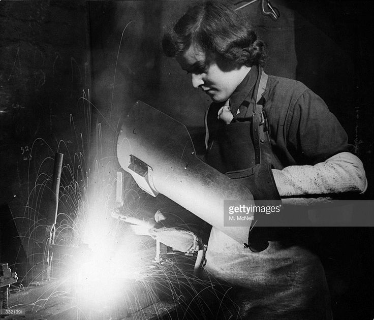 Peggy Hyland, a woman war worker, electric arc welding in one of Britain's largest shell-producing factories.