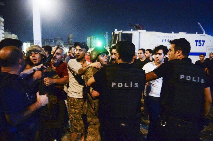 Turkish soldiers, arrested by civilians, are handed to police officers, in Istanbul's Taksim square, early Saturday, July 16, 2016
