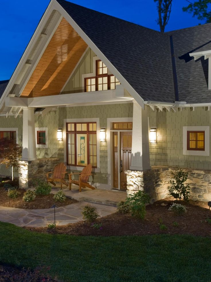 This Craftsman-style home has a large, inviting front porch accentuated by architectural details and woodwork. The low-pitched gabled roof, exposed beams, and stone and shingled siding are hallmarks of Arts and Crafts design.