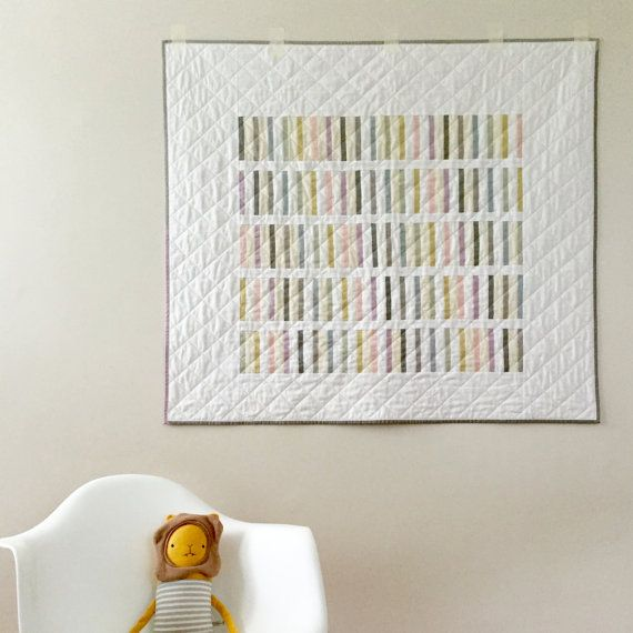 Inspired by Scandinavian interiors, this modern baby quilt features solid pastel stripes arranged in color order and set against a white background. The