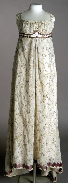 [via google translate] ca 1800-10 White muslin dress brocaded silk with gold cord chain stitch to drawing floral motifs, and garnished with an application of silk satin ribbon in purple diamond shaped and rectangular. Decorating with ribbon decoration is similar to wearing the dress of the Countess of Chinchon Francisco de Goya portrait in 1800. Museo del Traje.