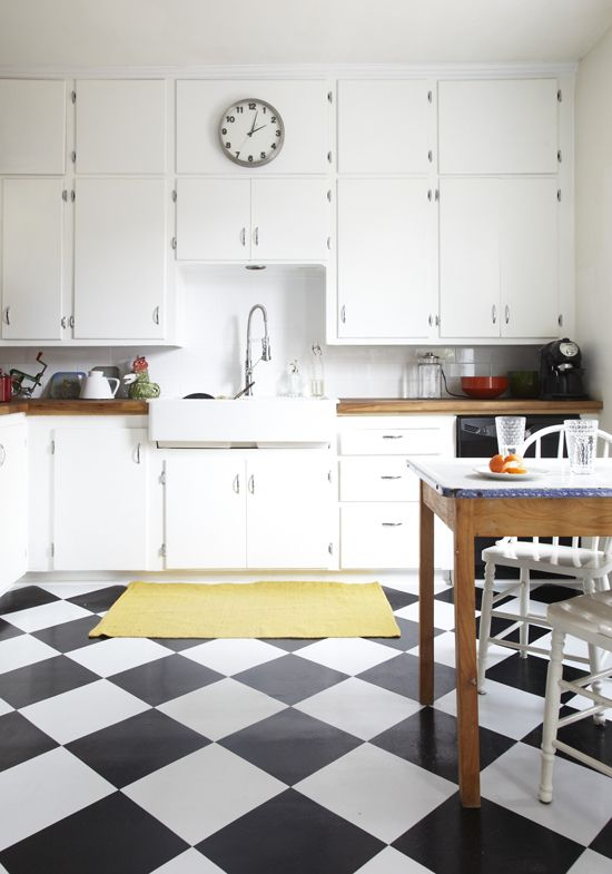 """""""One of the things that drew Ana and Christian to this house was the original 1950s cabinetry yet every contractor they spoke to insisted they tear it out and start again. Instead this couple chose to add in a black and white checked floor, a farmhouse style sink and butcher block countertops."""""""