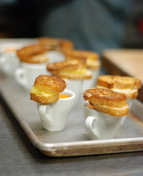 Mini grilled cheese sandwiches, served with tiny cups of creamy tomato soup for dipping!
