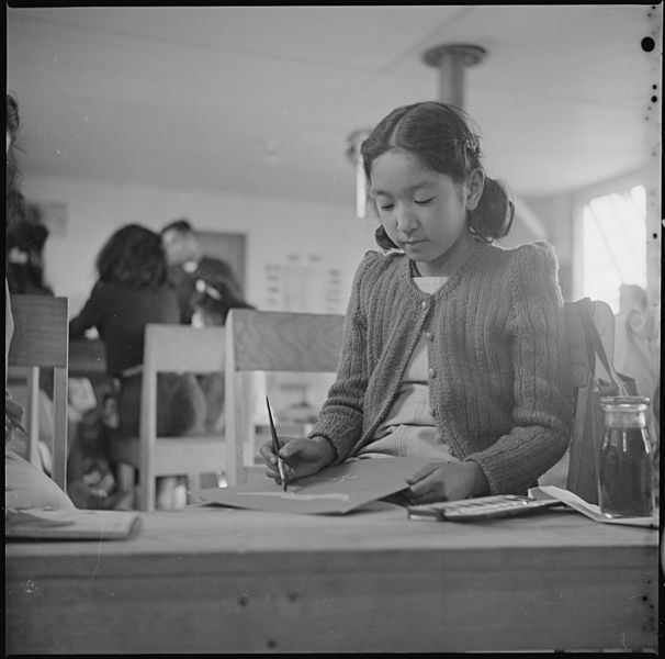 A sixth grade pupil in the classroom, Tule Lake Relocation Center, 3 November 1942, Francis Stewart, public domain via Wikimedia Commons.