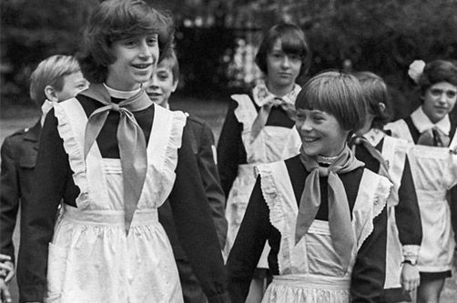 "Soviet school girls wearing uniform and ""pioneer"" ties. The white aprons were worn on state holidays and during the first day of school (September 1)."