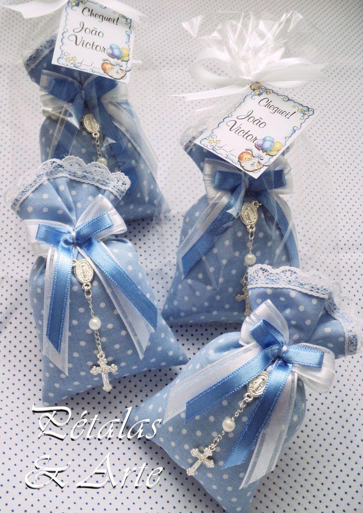 Sache Estampado Azul com Mini Terço. Os saches são decorados com laço de fita especial duplo, nas cores do tecido + mini terço. Cada sache vai embalado em saquinho celofane, fechado com laço de fita e tag personalizado.
