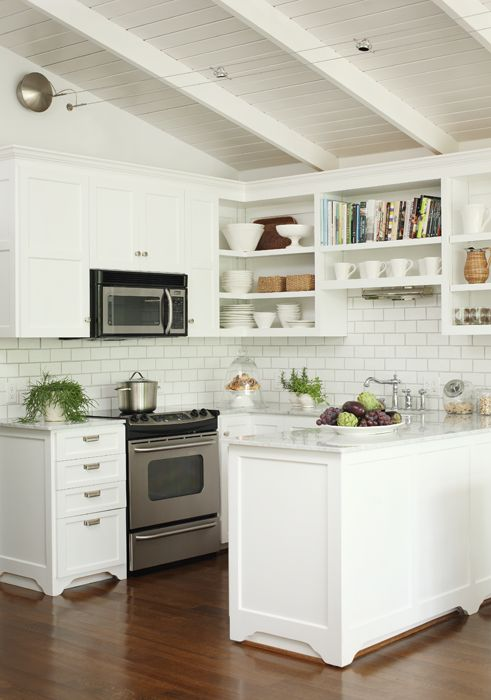 ... Kitchen In A Lake House With Marble Countertops, Stainless Steel  Appliances, Open Shelving, White Cabinets And White Subway Tile Backsplash