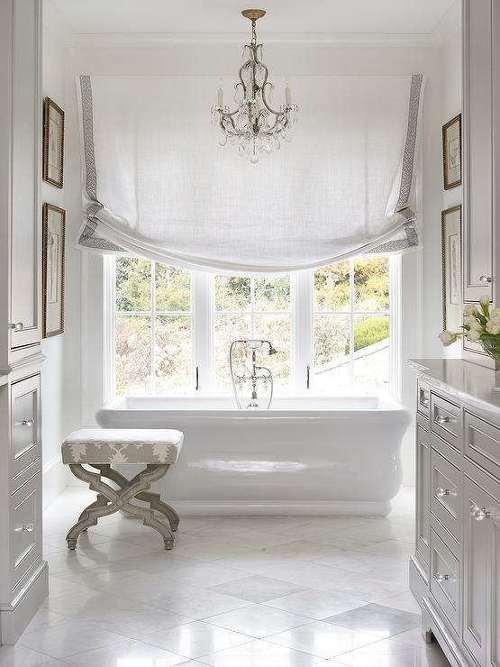 Stunning master bathroom features a crystal chandelier over a freestanding tub paired with a vintage style hand held tub filler placed in front of three windows dressed in one white roman shade accented with gray trim alongside a gray stool upholstered in Mary McDonald Garden of Persia Dove Fabric atop a white marble diamond pattern floor.
