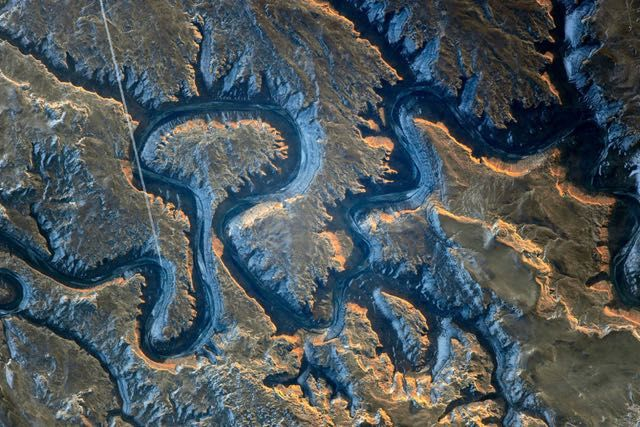 Green River Canyon – USA – 22 gennaio 2014  Le ripide scogliere del Green River (Utah), sono alte fino a 300 metri, e gettano un'ombra sull'acqua sottostante. Sulla sinistra la scia di un aereo in volo.