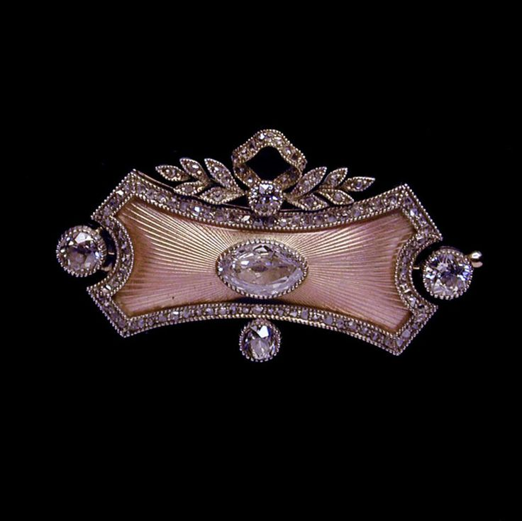 A pink enamel and diamond brooch by Fabergé, the oblong brooch with concave sides, translucent pink enamel on a rayed guilloché ground with marquise shaped diamond, with a fine border of rose cut diamonds millegrain-set in silver and a similarly set diamond laurel leaf and ribbon surmount. Workmaster Alfred Thielemann, St Petersburg, circa 1896 - 1908.