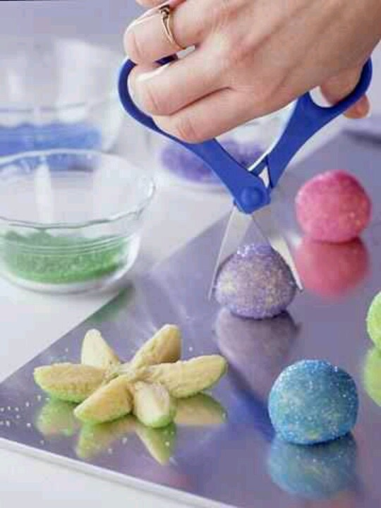 Roll a ball of sugar cookie dough in colored sugar.  Snip in half then snip each half into 3 petals. Gently spread petals apart and lay flat. Flip the pretty side up and follow the baking directions!