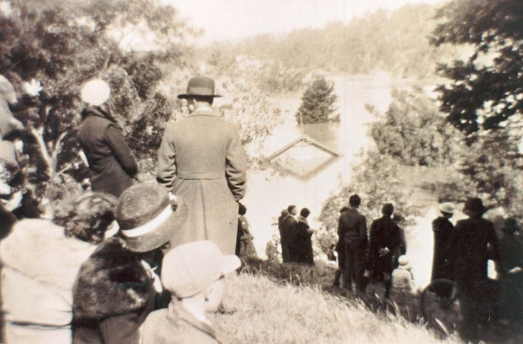 Crowds watch as the Yarra River in flood inundates the Fairfield Park Boathouse, 1934