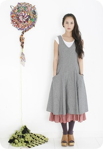 The Elaine Dress is elegant and simple with a fitted silhouette. It is made from 100% Japanese cotton and is fully lined with a cotton print that ruffles at the bottom. It has side pockets, a side zip, and check piping. Princess seams down the front give it a feminine shape and a line of buttons run thoughtfully down the back.