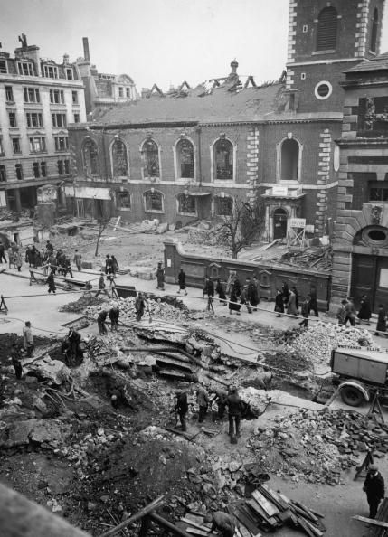Workmen repairing a hole in the road in Piccadilly, London, after a german bombing raid, 19th April 1941. The damaged St. James' Church can be seen in the background. (Photo by R.L. Court/Topical Press Agency/Hulton Archive/Getty Images)