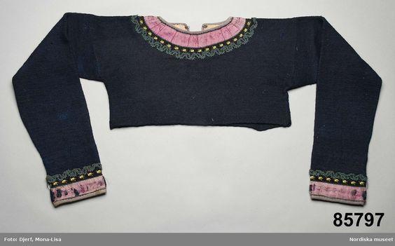 Kvinnotröja, mycket kort modell stickad av mörkblått tunt ullgarn.     Stickade tröjor fanns redan under 1700-talets första del i västra Skåne, men det är först under 1700-talets sista fjärdedel de blir mer vanliga. Ännu på 1840-talet  användes de i södra Skåne, men gick snart ur modet även där. Enstaka uppgifter om att de användes ännu senare i Torna härad.    Museets samling av stickade tröjor visar dock att de använts långt efter 1800-talets mitt.