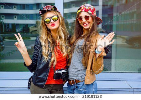 Bright stylish lifestyle urban portrait of two pretty best friends girls posing at leather jackets bright swag hats and sunglasses. Having faun, send you kiss and say hello.