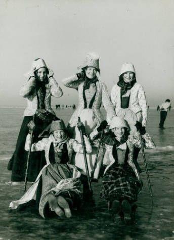 Vijf vrouwen in Hindelooper klederdracht, twee ervan zitten op priksleden, op het IJsselmeer bij Hindeloopen, foto 1954.