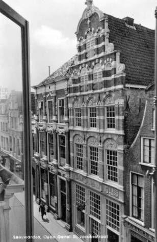 Een foto van de Sint Jacobsstraat in Leeuwarden uit ca. 1960. Het pand waar juist een man voorbij loopt betreft het voormalige hotel 'De Phoenix', waar de SD-ers na aankomst in Leeuwarden eerst werden ondergebracht. Een saillant detail is dat ditzelfde pand na de oorlog een tijd lang als onderkomen voor het Oorlogstribunaal heeft gediend.