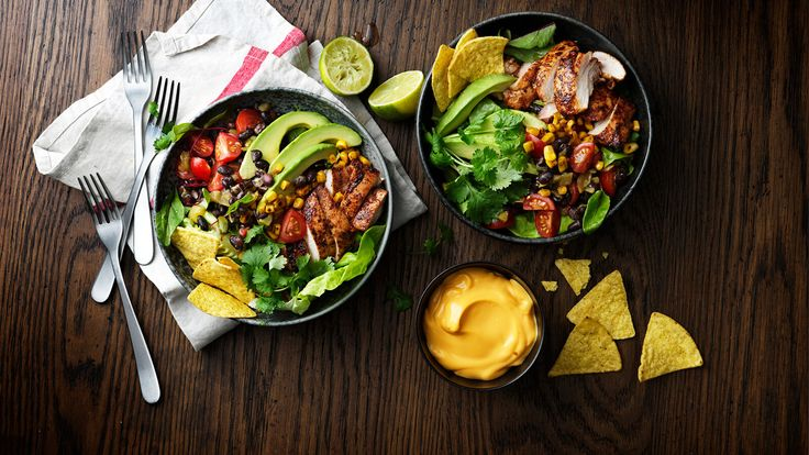 Oppskrift på en salat med tacokrydret kylling, servert med tortilla chips og ostdipssaus.