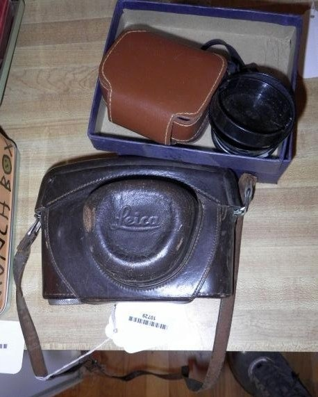 CAMERA LEICA-METER MC, CAMERA WITH ATTACHED LENS AND CASE, SLIGHT CONDITION ISSUE TO BLACK LEATHER UNDERNEATH OF LENS, ALSO INCLUDES EXTRA ACCESSORIES