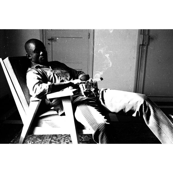 """Relax nigeriano. Opera dell'archivio dell'agenzia """"D.F.P"""", fondata da Dani Maria Turriccia nel 1963. La fotografia appartiene a un reportage, condotto in Nigeria nel 1975.Momento di relax all'interno di una dimora nigeriana. La luce, che filtra dalla finestra, nasconde il volto dell'uomo, irradia i contorni della poltrona e il fumo del sigaro. Composizione ipotattica: è un intreccio di linee verticali ed orizzontali."""