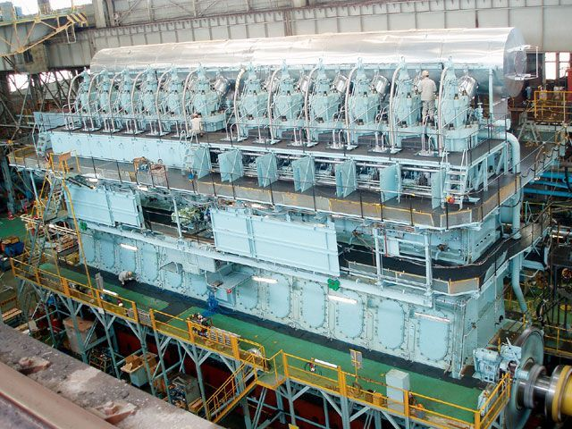 12-cylinder two-stroke diesel ship engine rated at 100,000 horsepower manufactured at Kawasaki's Kobe Works. Note the two workers on the top portion of the engine to get an idea of how huge the engine is.    Read more: http://www.sportrider.com/features/146_0711_kawasaki_heavy_industries/photo_15.html