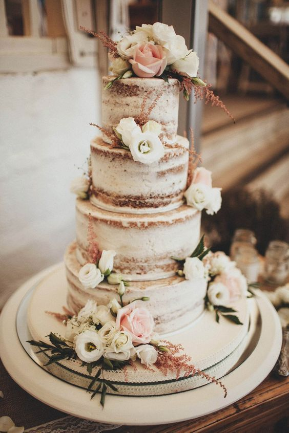 Non-iced, or just partial iced, wedding cakes are very popular this year. Add some roses to give it a stunning natural look.