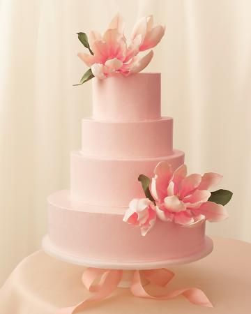 Magnolia blossoms shaped from gum paste stand in for real blooms that are too delicate to use as a cake topper