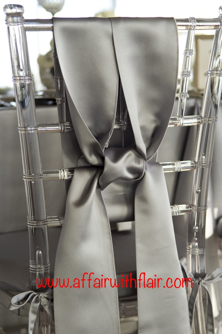 Silver satin chair ties were uniquely tied around this lucite chivari chair.