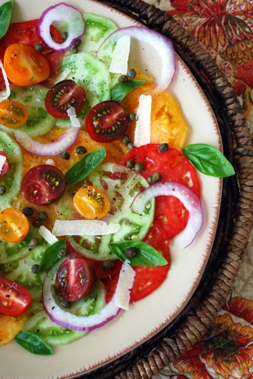 Heirloom Tomato Carpaccio Salad.  Heirloom tomatoes~ sliced extremely thin~ with onion, capers, shaved parmesan, basil, olive oil, salt & pepper. You can also add pine nuts, shaved fennel, or balsamic vinegar.