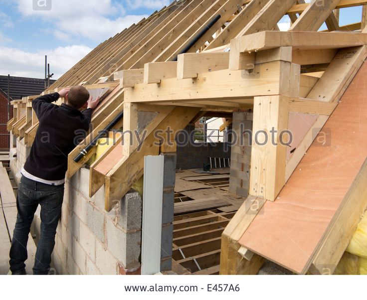 self building house, constructing roof, insulating dormer cheeks with sheet insulation Stock Photo
