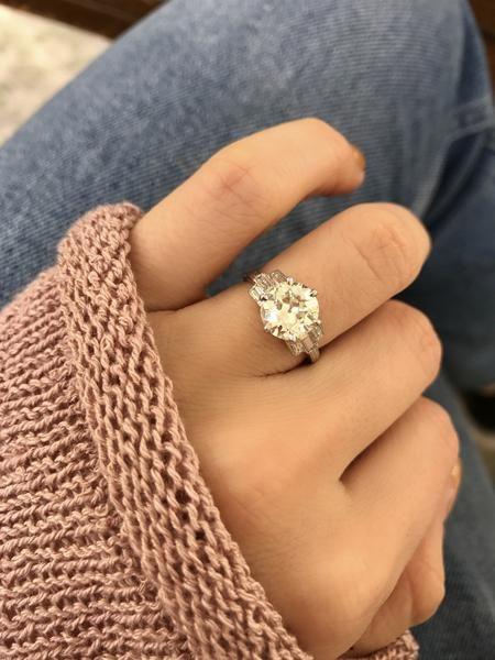 This gorgeous diamond engagement ring circa 1930 features a beautiful 1.92 ct diamond with 3 baguettes to each side in a platinum band with hand engravings.