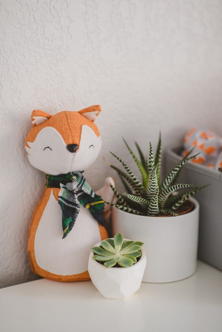 Plush fox and succulents in white geometric succulent pots from our woodland adventure themed nursery in grey, white, orange, and mint.