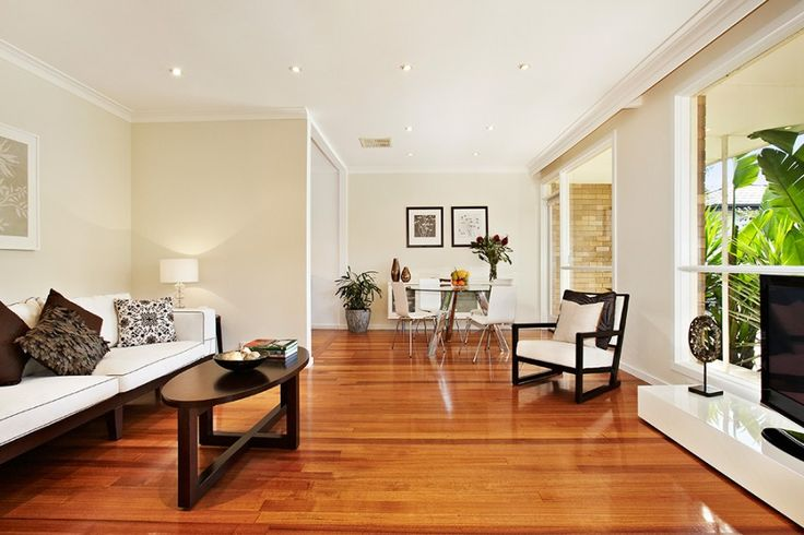 Modern open plan living room and dining. Very clean and neutral looking palettes and polished floorboards.