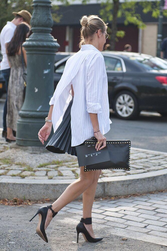 Back slit white tailored shirt, black pleated skirt, black ankle strap heels and black studded clutch