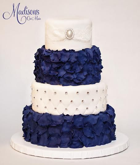 Ruby's wedding cake! Hand cut navy blue fondant petals, with quilting and rhinestones on the third tier, along with lace and a brooch on the top tier! Photo by Kevin Paul Photography!