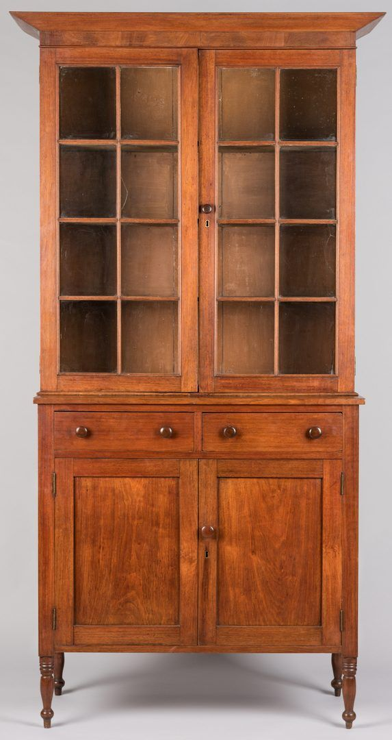 """Middle Tennessee Jackson Press, attr. Davidson County, walnut with poplar secondary, the top section having a slanted cornice over a figured walnut or mahogany frieze, two glazed doors with total of 16 panes opening to three shelves, and a lower section with paneled sides and two drawers having dovetailed sides and round knobs over two doors with figured wood panels, atop short turned legs. Right side drawer has penciled initials MV on the back. 93"""" H x 48 1/2"""" W x 19 1/4"""" D."""