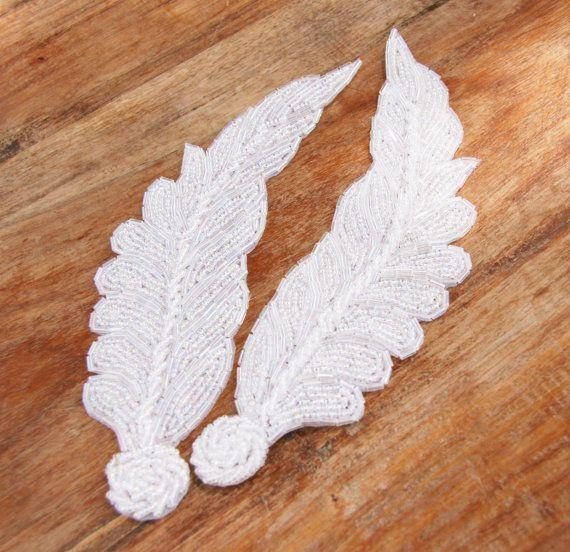 Beautiful mirrored pair of beaded feather appliques, made with iridescent white glass beading on fabric backing.  Wonderful for wedding/event projects, DIY, head pieces, sashes, etc.  Available in other colors!