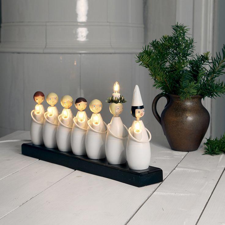 Flott og sjarmerende elektrisk lysestake fra Star Trading som er utrolig populær! Luciatog Lysestake består av 7 søte barn i hvitt med hvert sitt lys. Kombinasjonen av det søte uttrykket og bruken av enkle og solide materialer i rene farger scorer høyt i fleste hjem og gjør dette til en sikker vinner. Luciatoget ble designet av Sten Bengtsson (1915-1991). Han var en kjent belysningsarkitekt på Ateljé Lyktan under 1950- og 60-tallet.