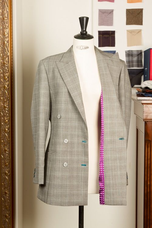 A 6 button double breasted ladies suit; Prince of Wales check with matching blue details, peaked lapels and a festive purple/white polka dot lining; Anthracite trousers with a baby blue chalk stripe and a medium turn-up. Een 6 knoops double breasted dames kostuum; Prince of Wales check met bijpassende blauwe details, peaked lapels en een feestelijke paars/wit polka dot lining; Antraciet pantalon met baby blauw krijtstreep en een medium omslag.